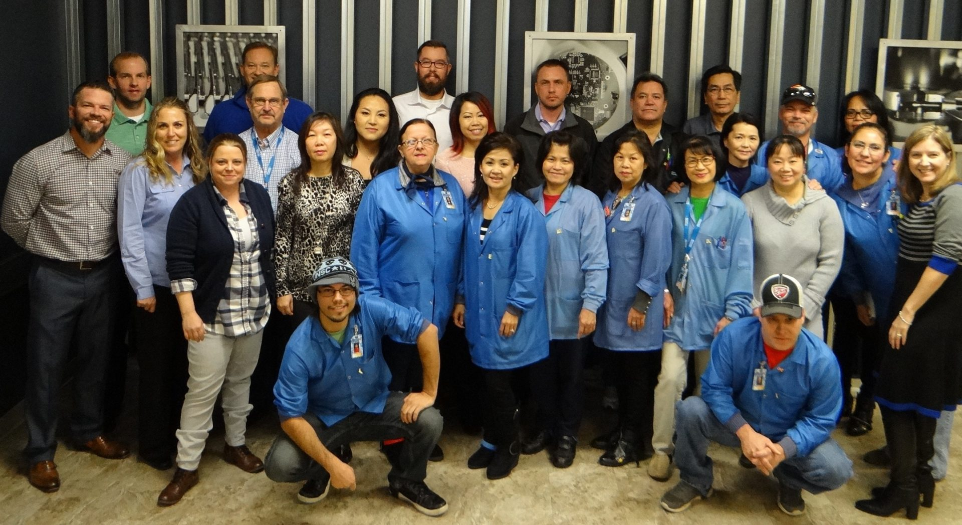 group photo of Advanced Assembly employees in blue jackets